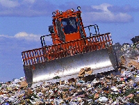 A bulldozer working on a rubbish dump.