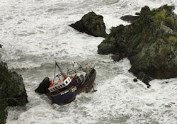 A ship stuck on rocks in a storm