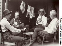 Four men site playing cards, an image taken about 1908-09; the photographer, Frank Sadorus (1880-1934), is second from left. From the collection of the Illinois State Museum.