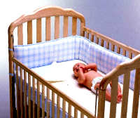A baby in a smart wooden crib.