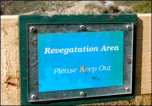 A small blue sign on a fence post says 'Revegatation Area Please Keep Our'.